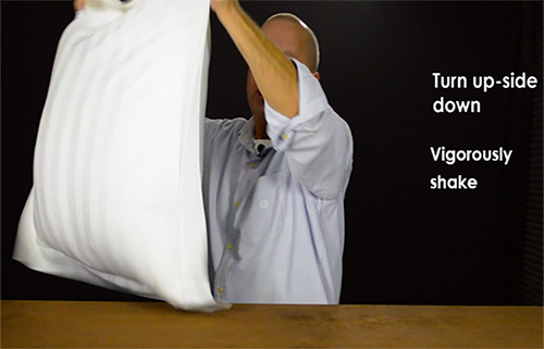 Shaking the pillow insert to the top of the sham